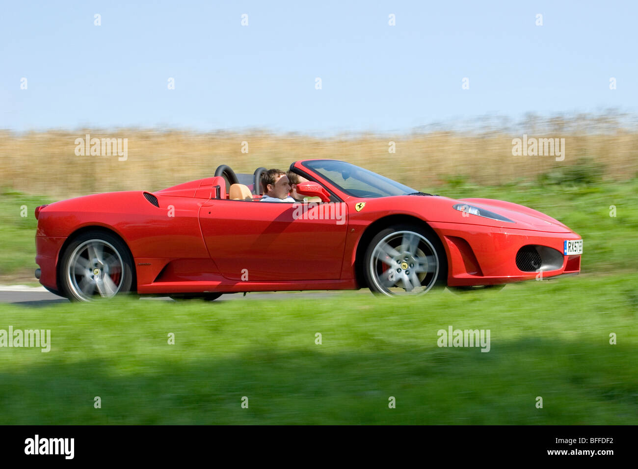 Low angle profile (side view) of a Red Ferrari 360 Spider supercar in motion on the public roads driving fast - Stock Image