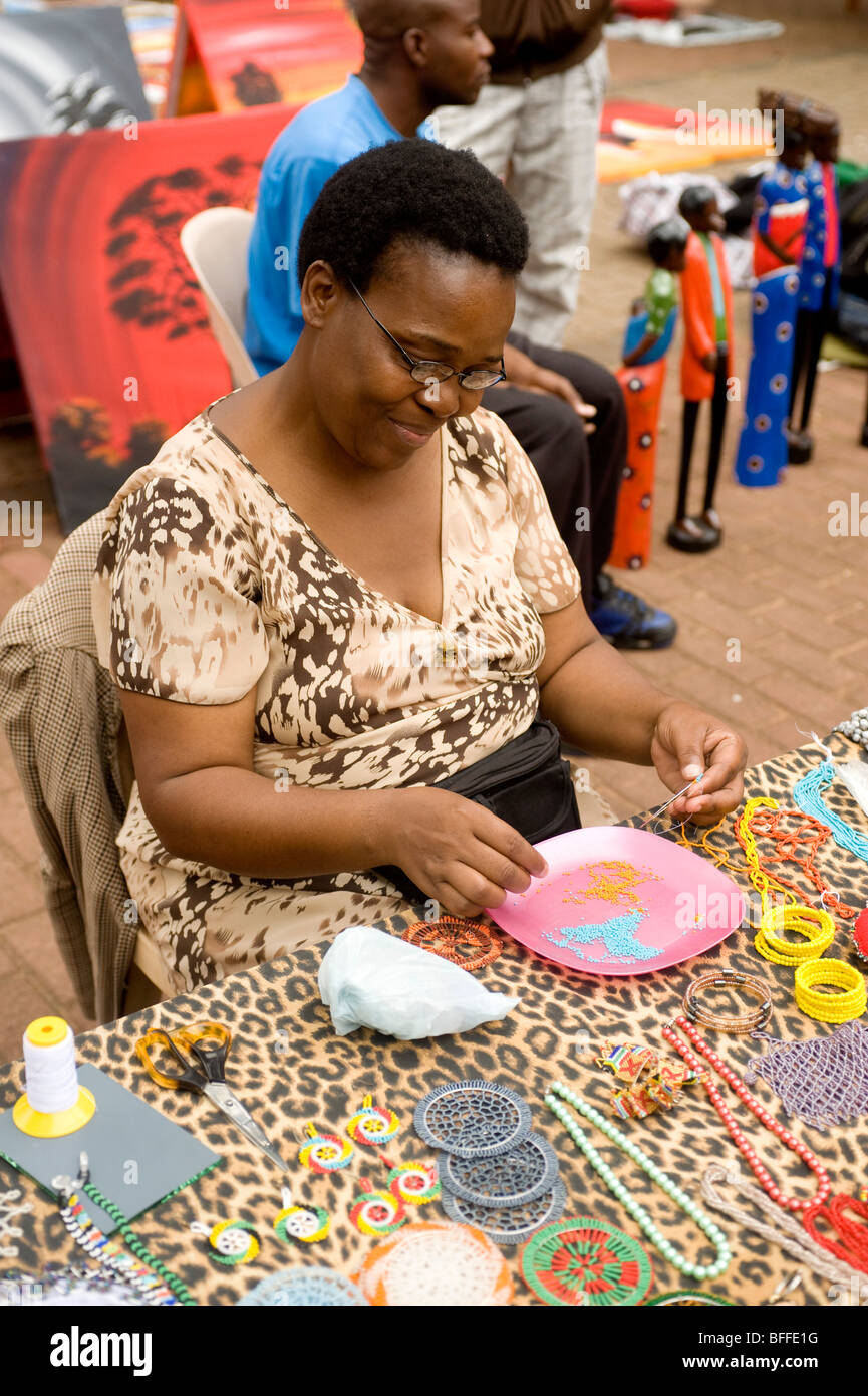 Woman making bead neck laces. Essenwood Park Street Market. Durban, South Africa - Stock Image