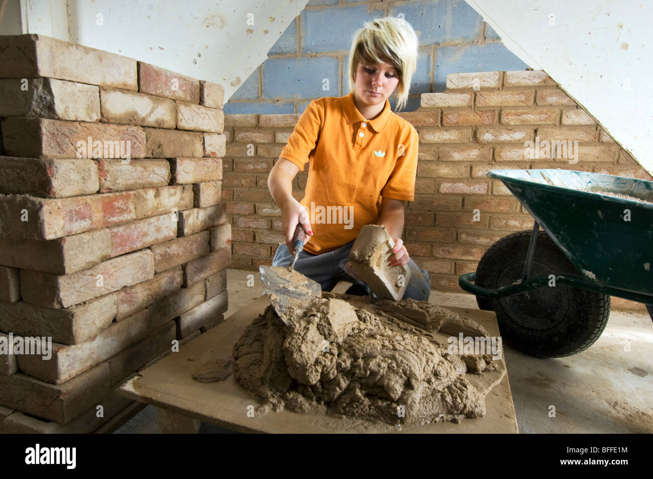 Girl student learning practical bricklaying  at a City College - Stock Image