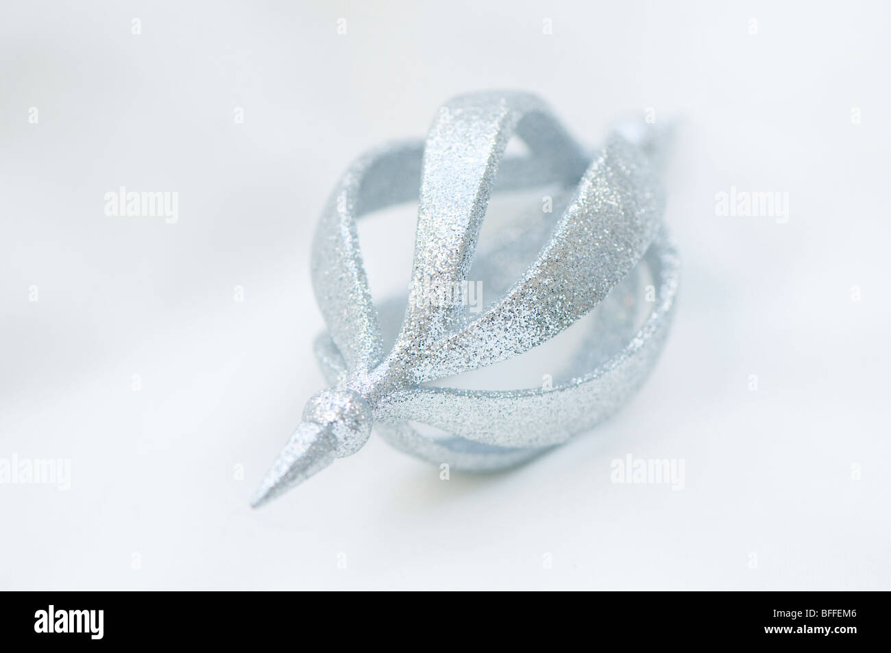 Silver glittery Christmas decoration against a creamy white background - Stock Image