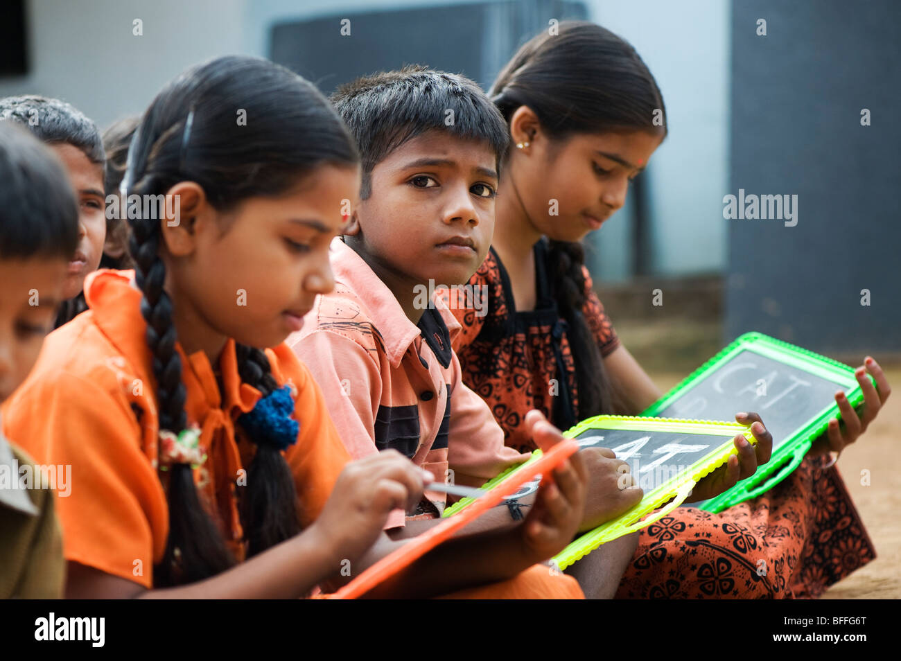 Indian school children sitting outside their school writing on chalkboards. Andhra Pradesh, India. Selective focus. Stock Photo