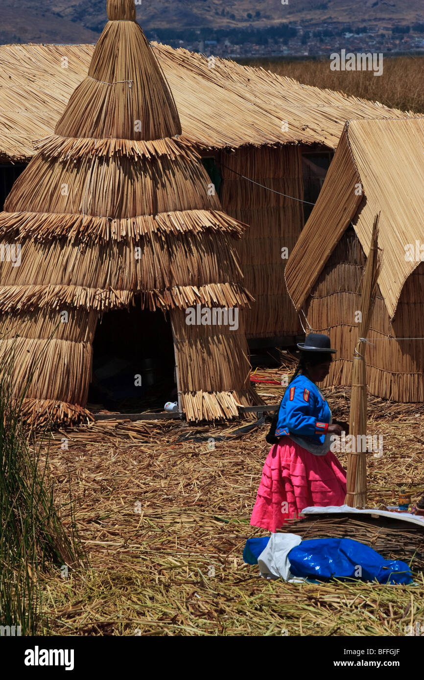 A female inhabitant infront of the huts made of reed on one of the Uros floating islands of Lake Titicaca Stock Photo