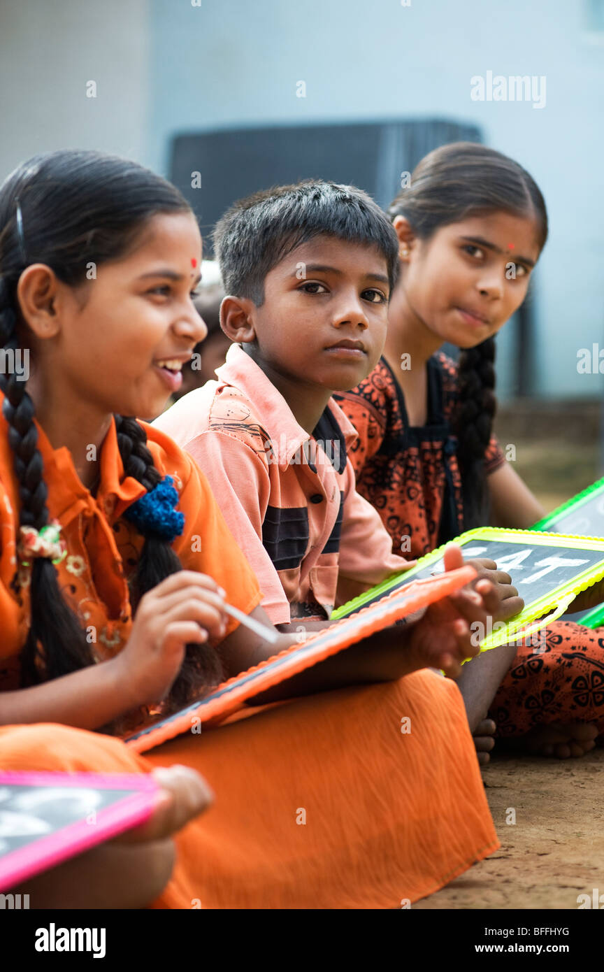 Indian school children sitting outside their school writing on chalkboards. Andhra Pradesh, India. Selective focus Stock Photo
