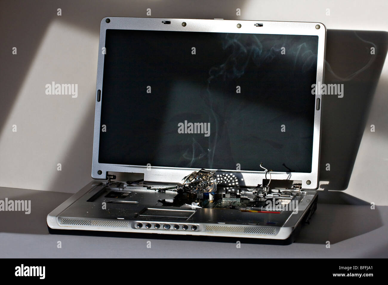 Broken Laptop Computer. Screen cracked with smoking computer components. Stock Photo