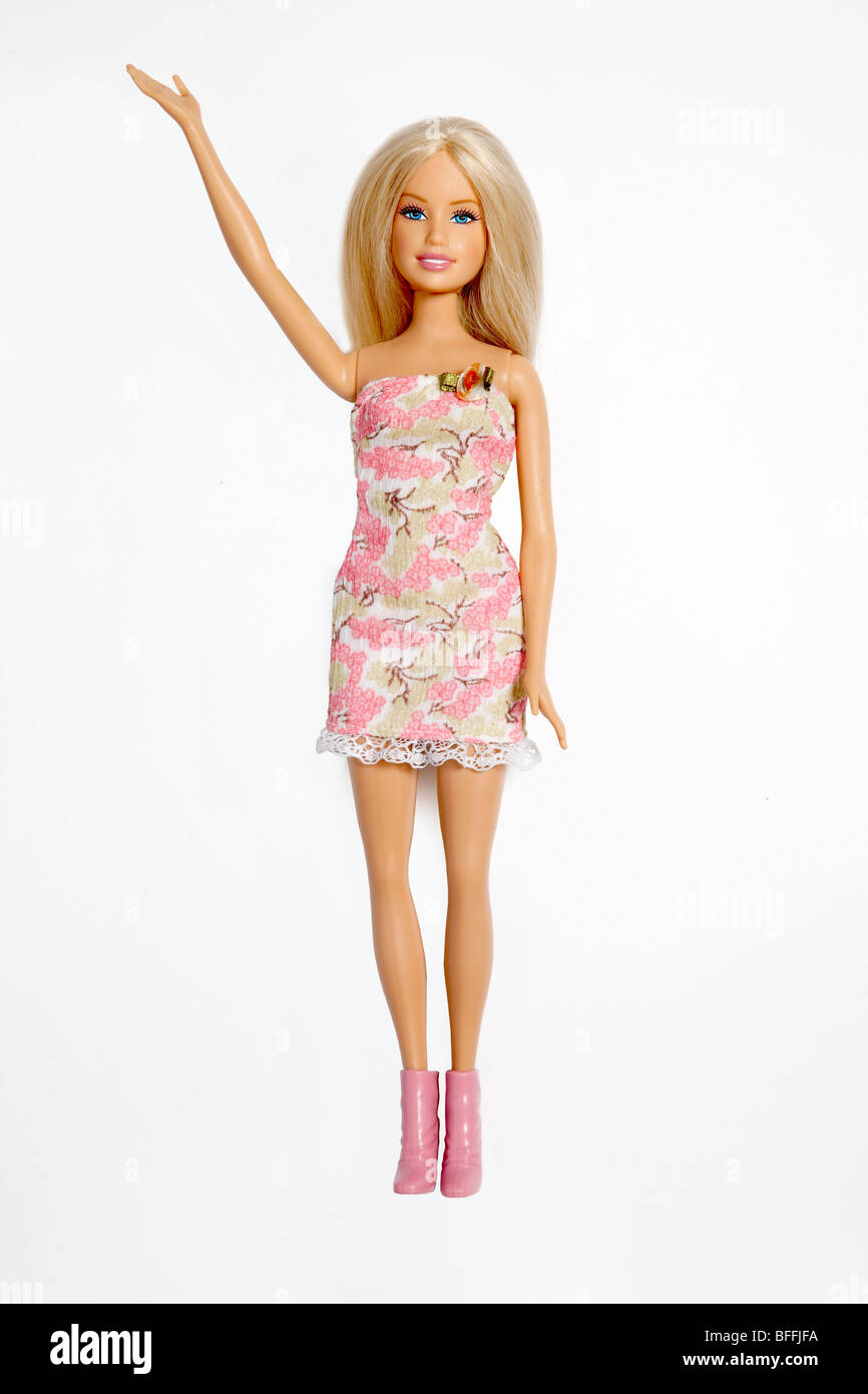 Barbie Doll wearing pink dress and boots with arm raised - Stock Image