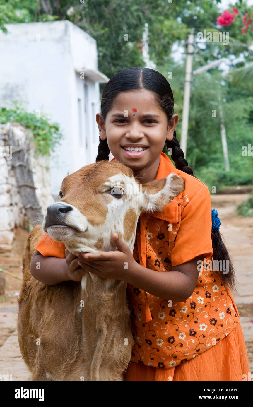 Young Indian village girl hugging a calf in a rural Indian village. Andhra Pradesh, India - Stock Image