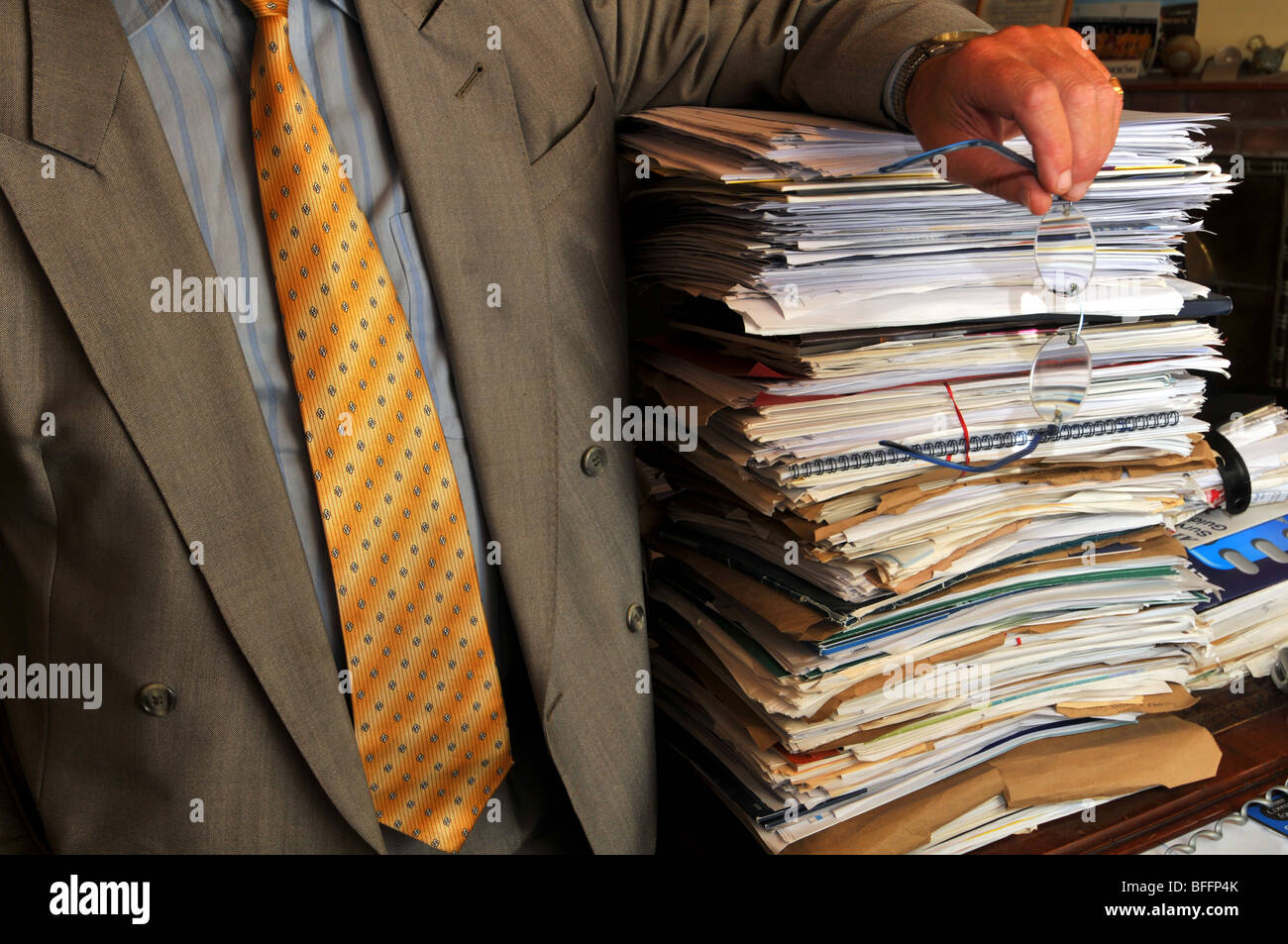 Businessman leaning on a stack of paperwork, overworked office worker or manager with pile of documents - Stock Image