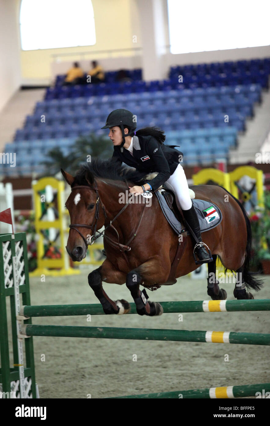 A Kuwaiti woman showjumper in action at an international tournament at QEF's indoor ring in New Rayyan, Doha, - Stock Image