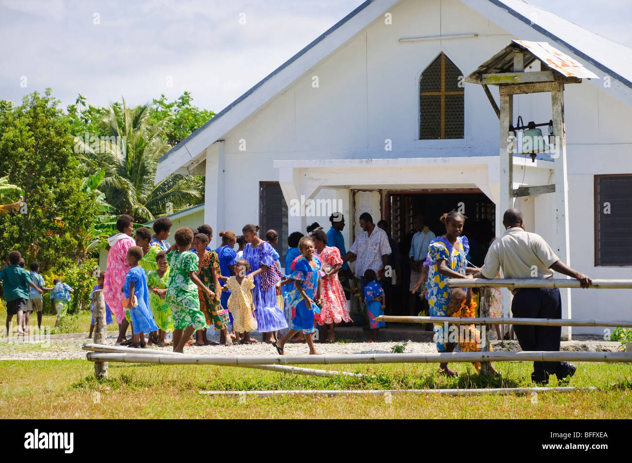 Brightly dressed ladies leaving church. - Stock Image