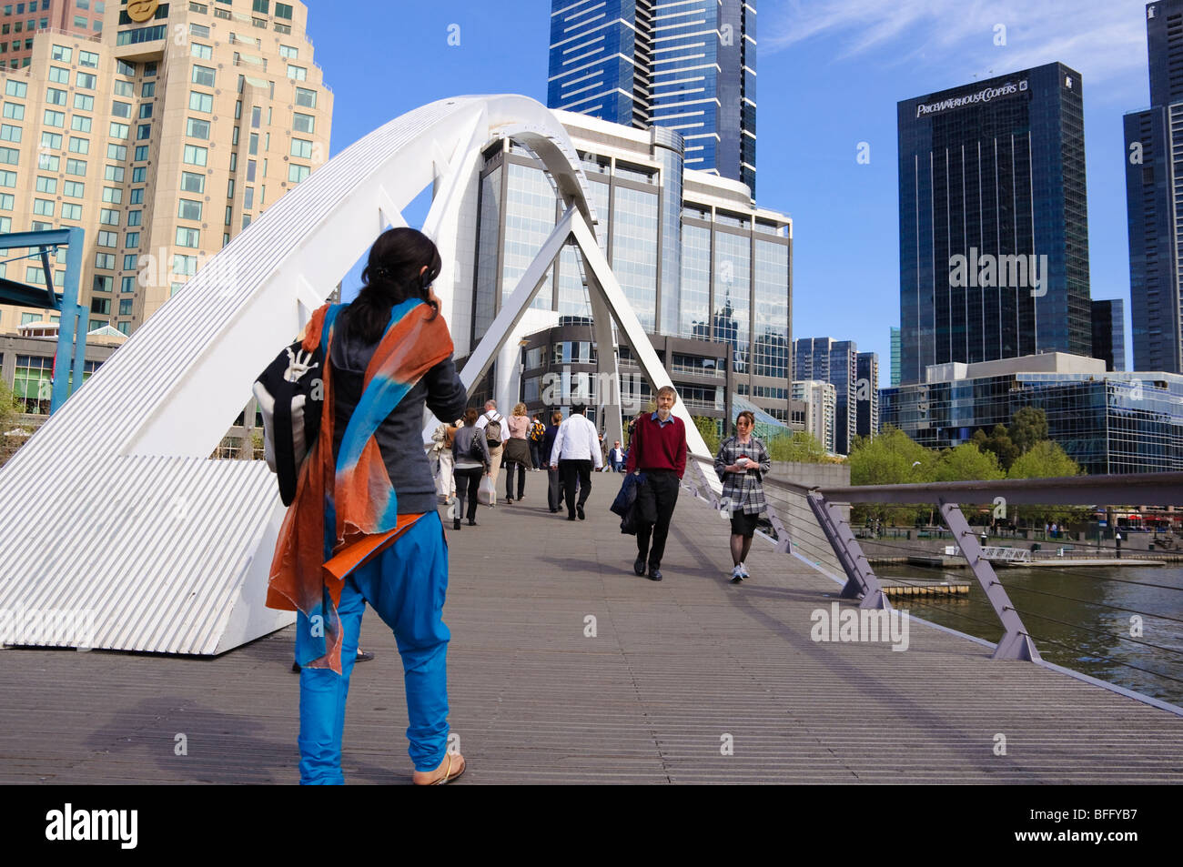 Migrant crossing a pedestrian bridge. - Stock Image