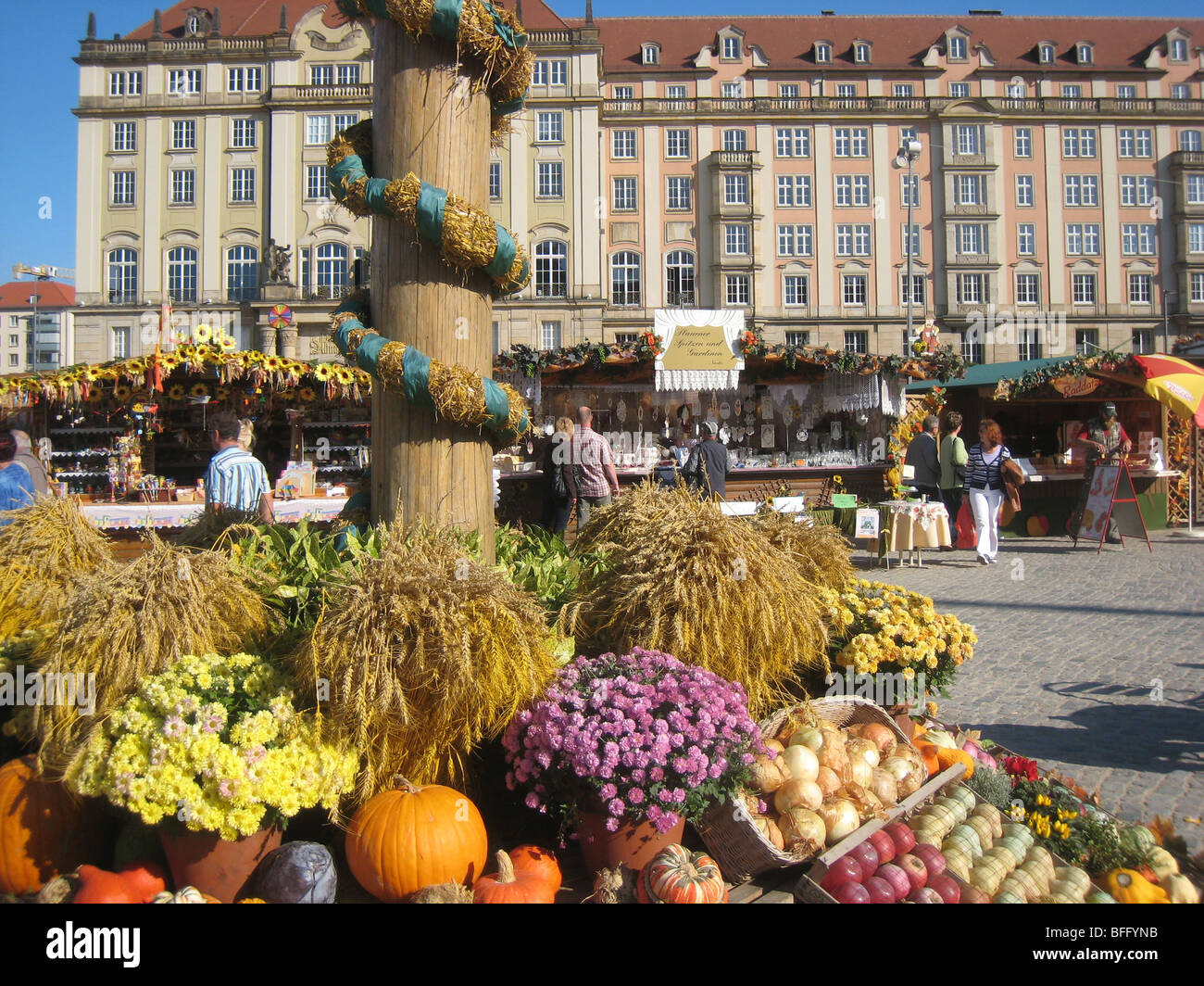 Fruit, flowers, and vegetables at foot of decorative flag pole erected for an Autumn fair in the centre of Dresden - Stock Image