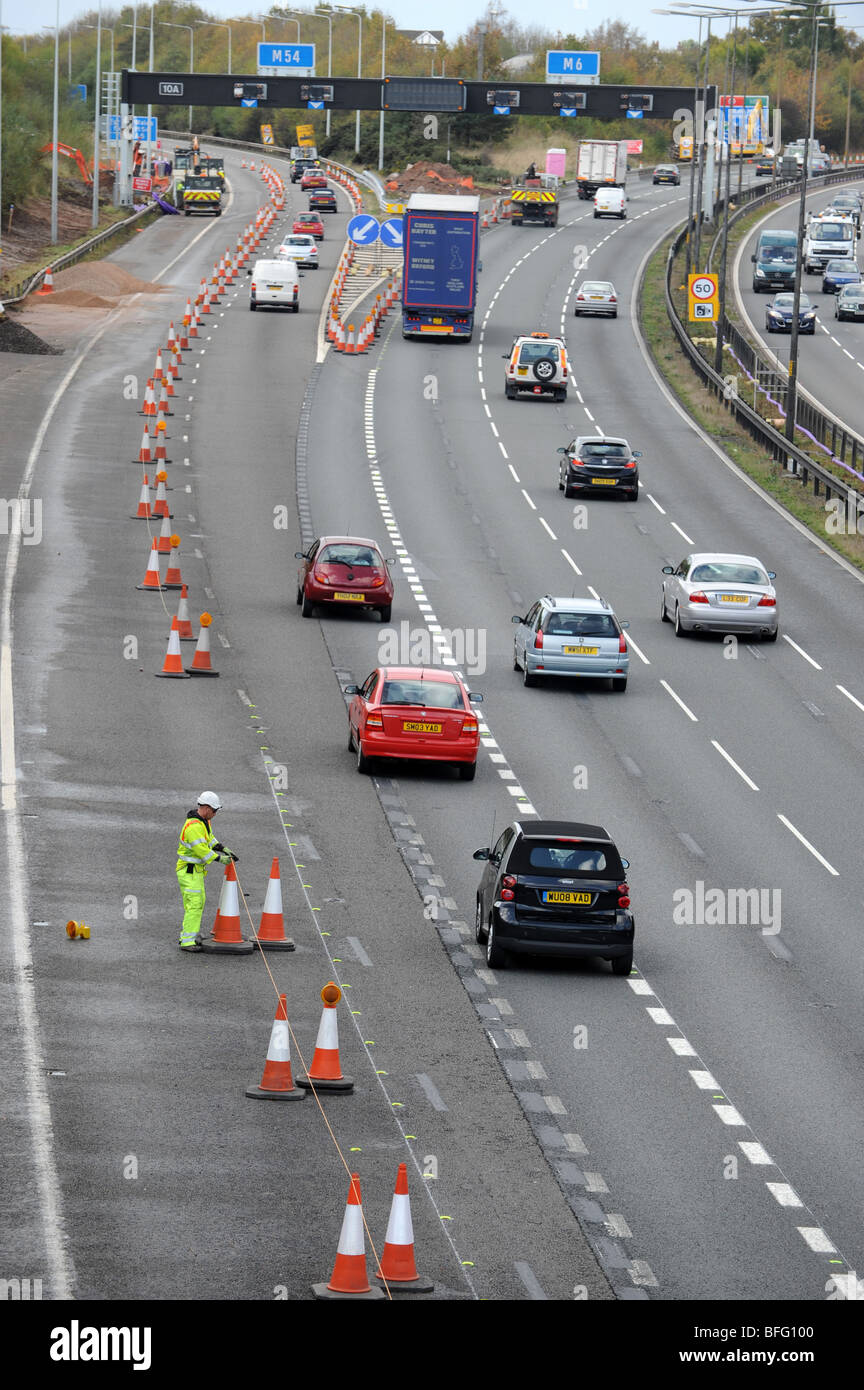 Highways worker putting traffic cones on M6 motorway junction with the M54 - Stock Image