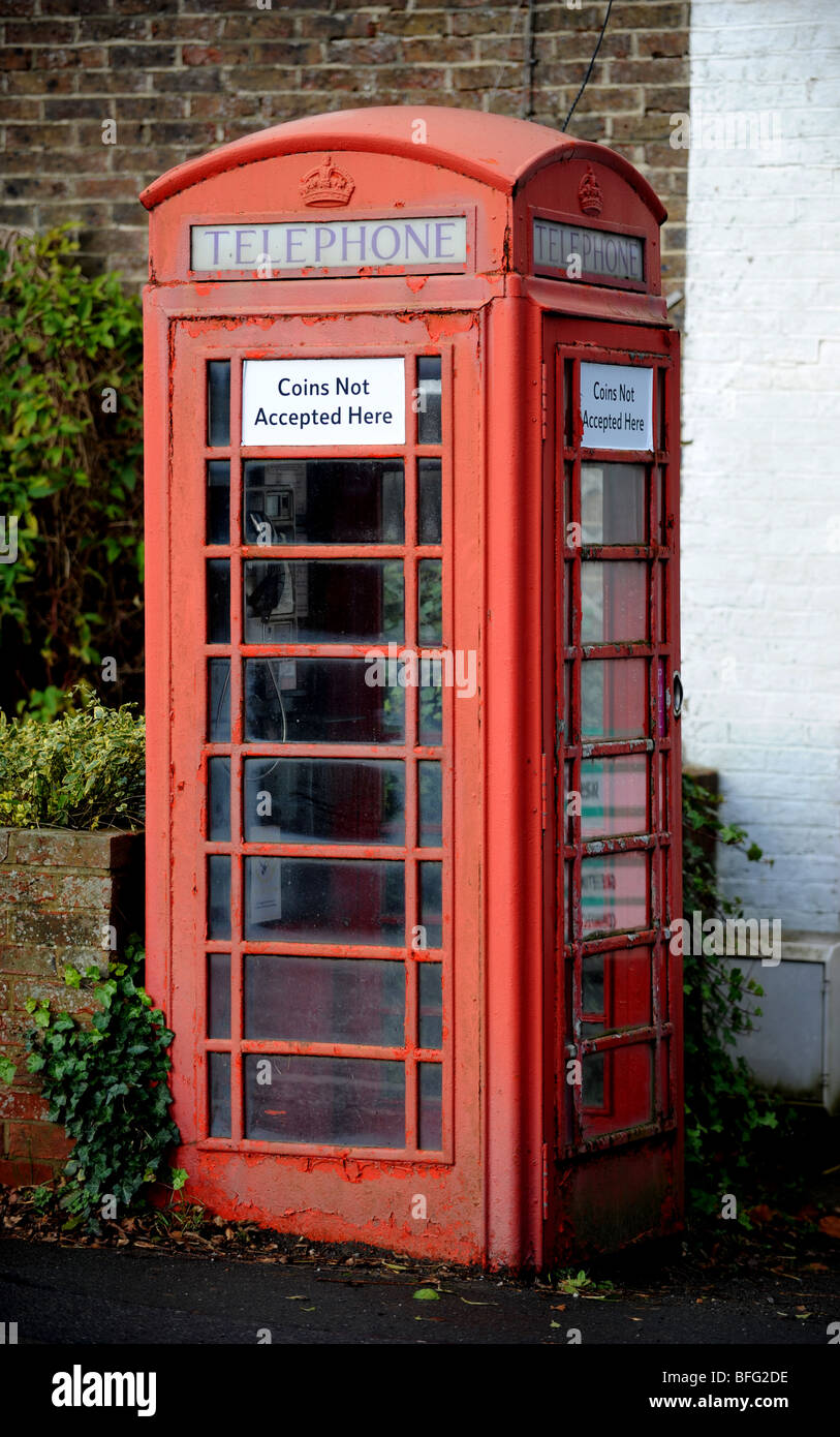A red telephone box  which no longer accepts coins - Stock Image