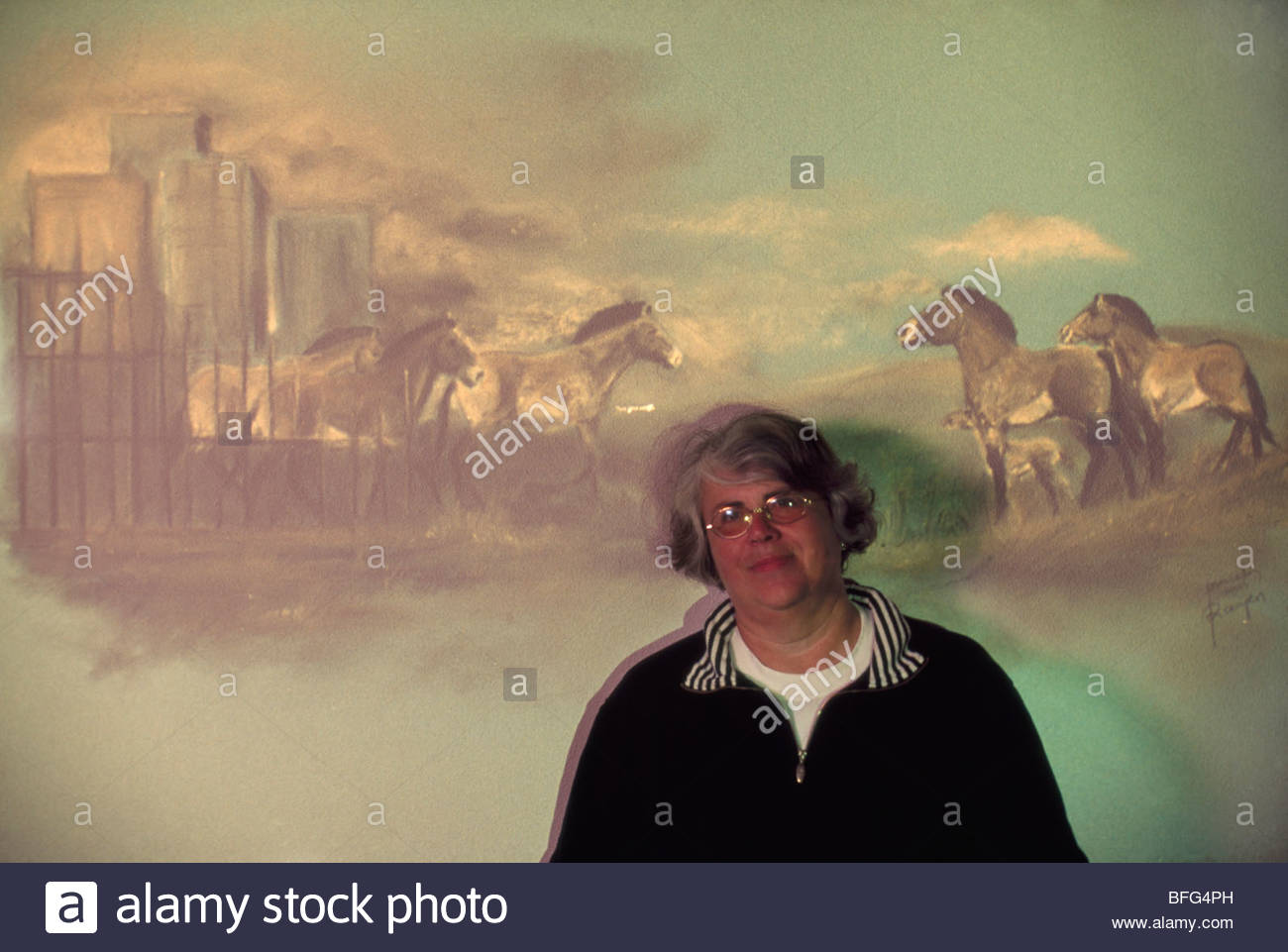 Inge Bouman poses in front of painting illustrating transfer of takhis from captivity to freedom, Hustain Nuruu - Stock Image