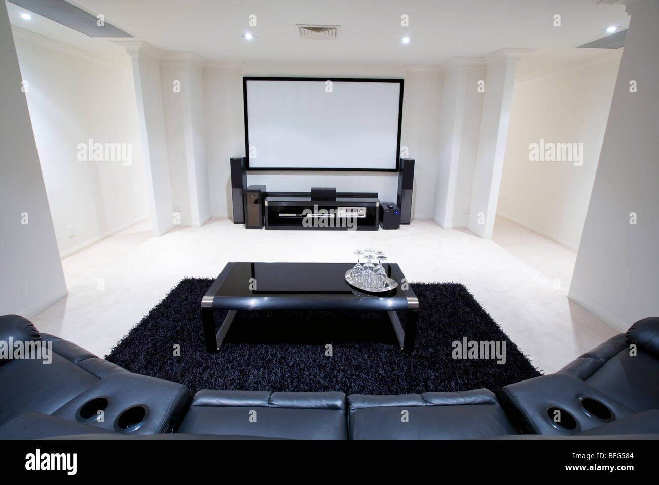 home theater room with black leather recliner chairs black rug and