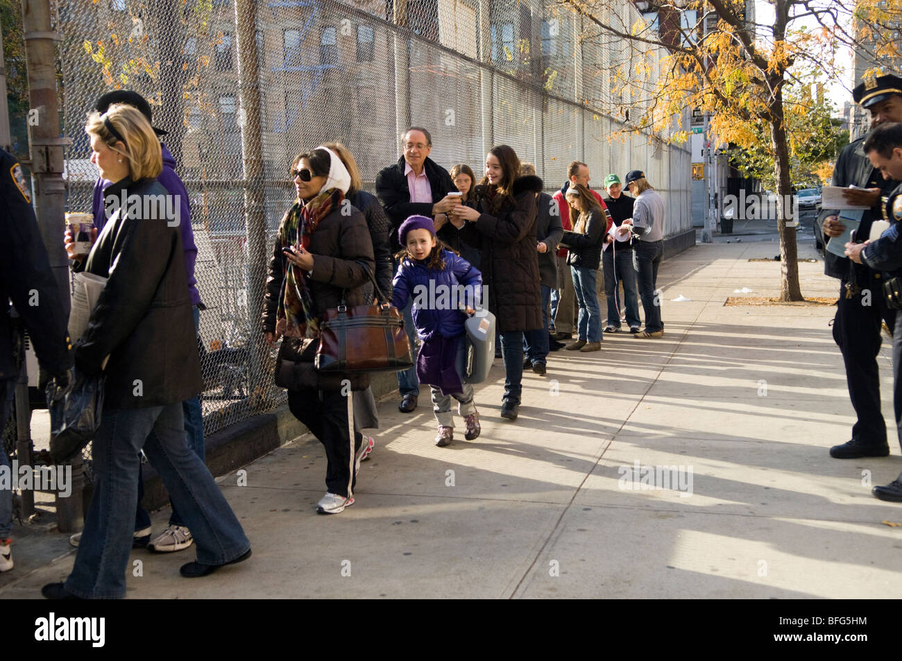 Children accompanied by parents and guardians line up to receive the free H1N1 influenza vaccine - Stock Image