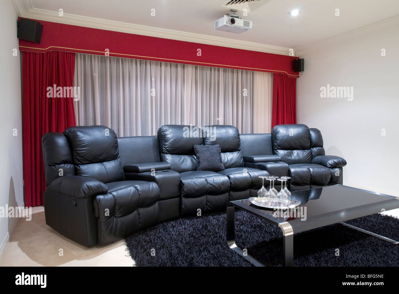 Home Theater Room With Black Leather Recliner Chairs, Red Curtains, Black  Rug And Table With Wine Glasses