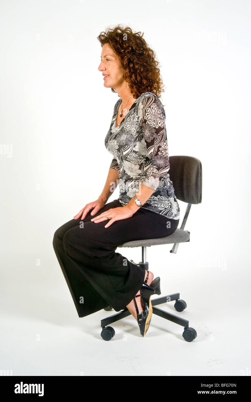 Sitting with ankles locked indicates apprehension in this woman in 'body language' terms. - Stock Image