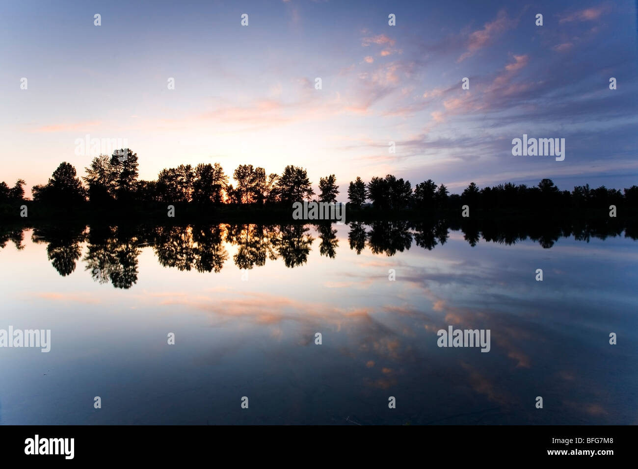 Clouds reflect in a river in Carburn Park in Calgary Alberta at sunset. - Stock Image