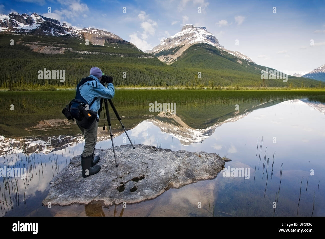A Photographer sets up a morning landscape photo at Rampart Ponds in Banff National Park, Alberta, Canada - Stock Image
