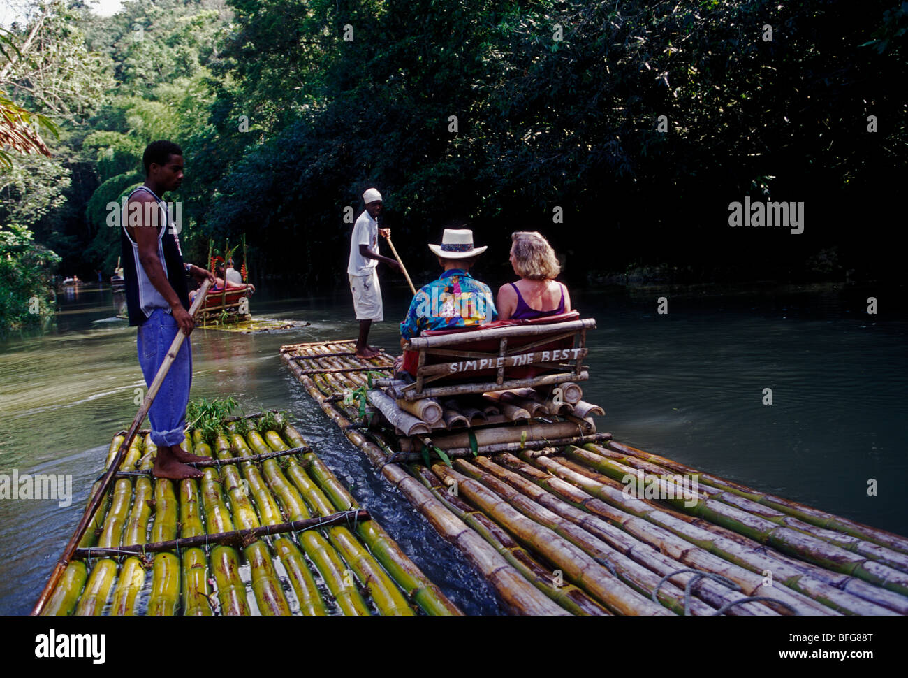Jamaican man, adult man, tour guide, tourists, couple, bamboo raft, bamboo raft trip, The Great River, Great River, - Stock Image