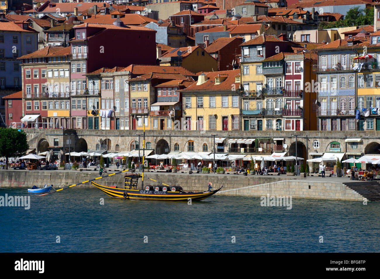 Porto, houses and street restaurants in the Ribeira district with a Port Wine barge - Stock Image