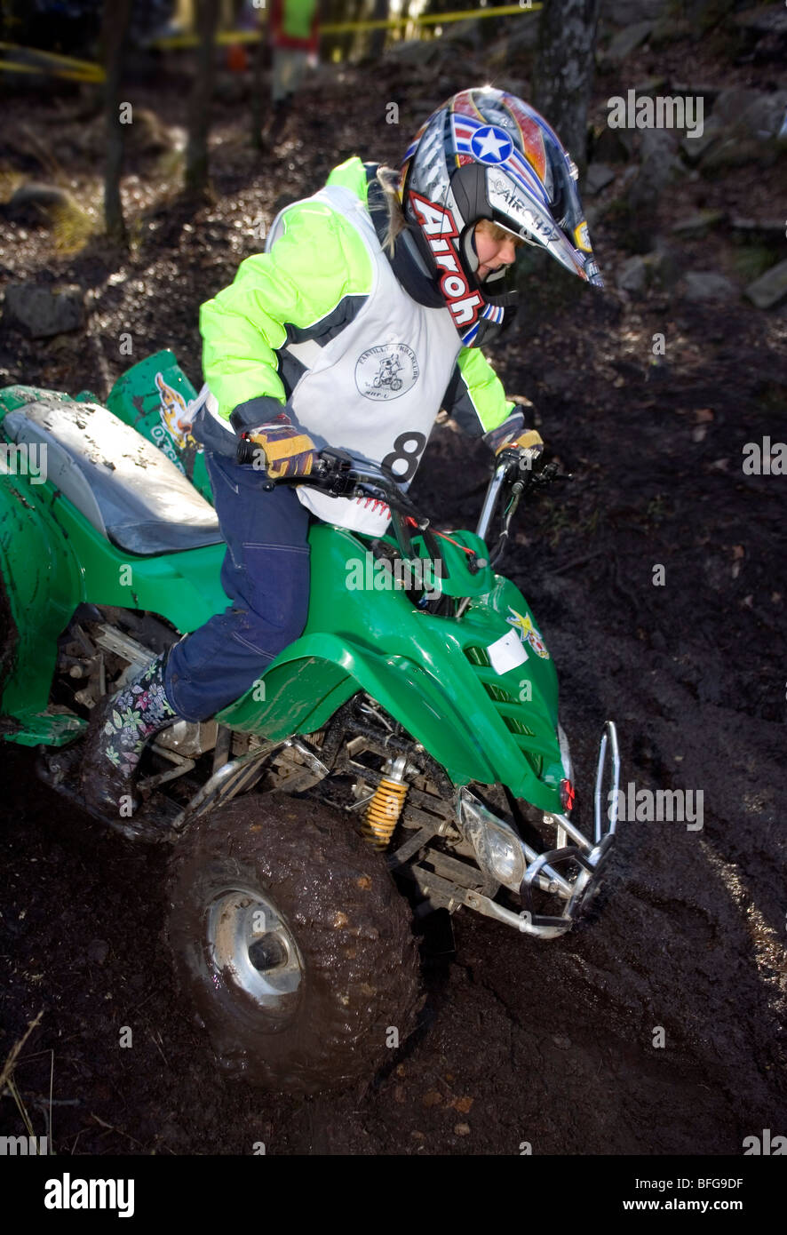 Yong girl in full protective wear rides downhill all-terrain vehicle - Stock Image