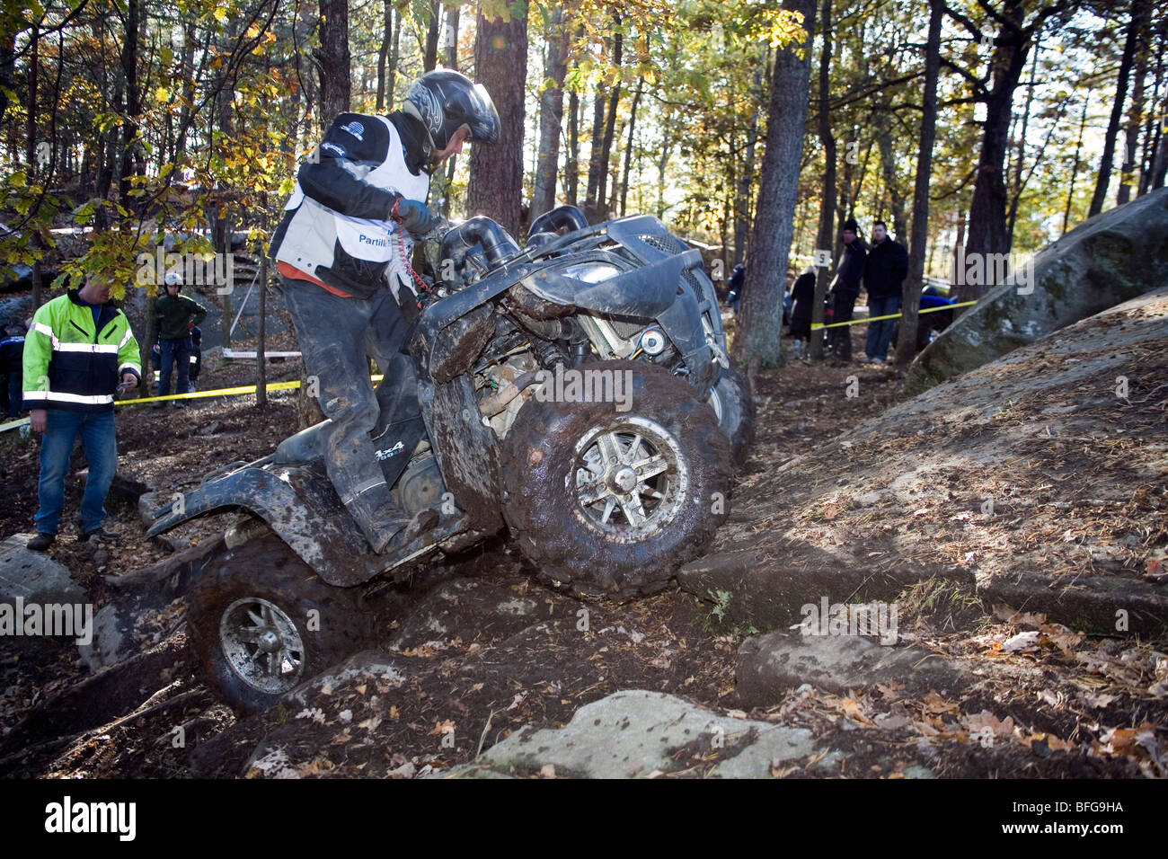 Man rides all-terrain vehicle (ATV) on steep uphill terrain in woods. Trial off-road biking. Sweden. - Stock Image