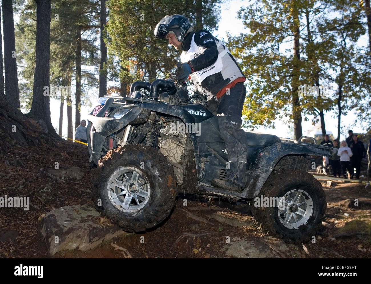 Man rides all-terrain vehicle (ATV) on rocky terrain in woods. Trial off-road biking. Sweden. - Stock Image