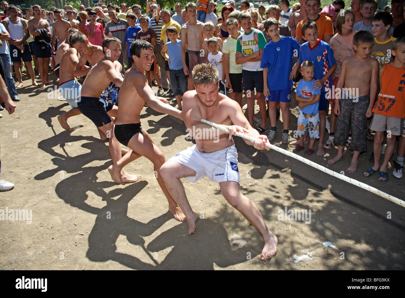 A team of boys pulls rope on a beach in a tug of war watched by crowd of spectators. - Stock Image