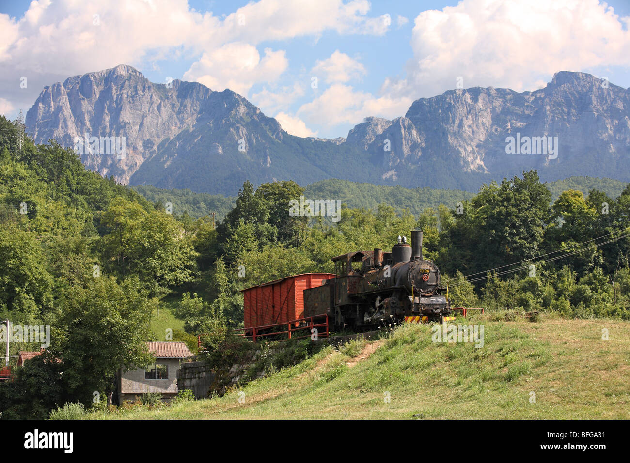 Bosnia and Herzegovina; Jablanica district. Old steam locomotive displayed in outdoor museum. In background Mountain - Stock Image