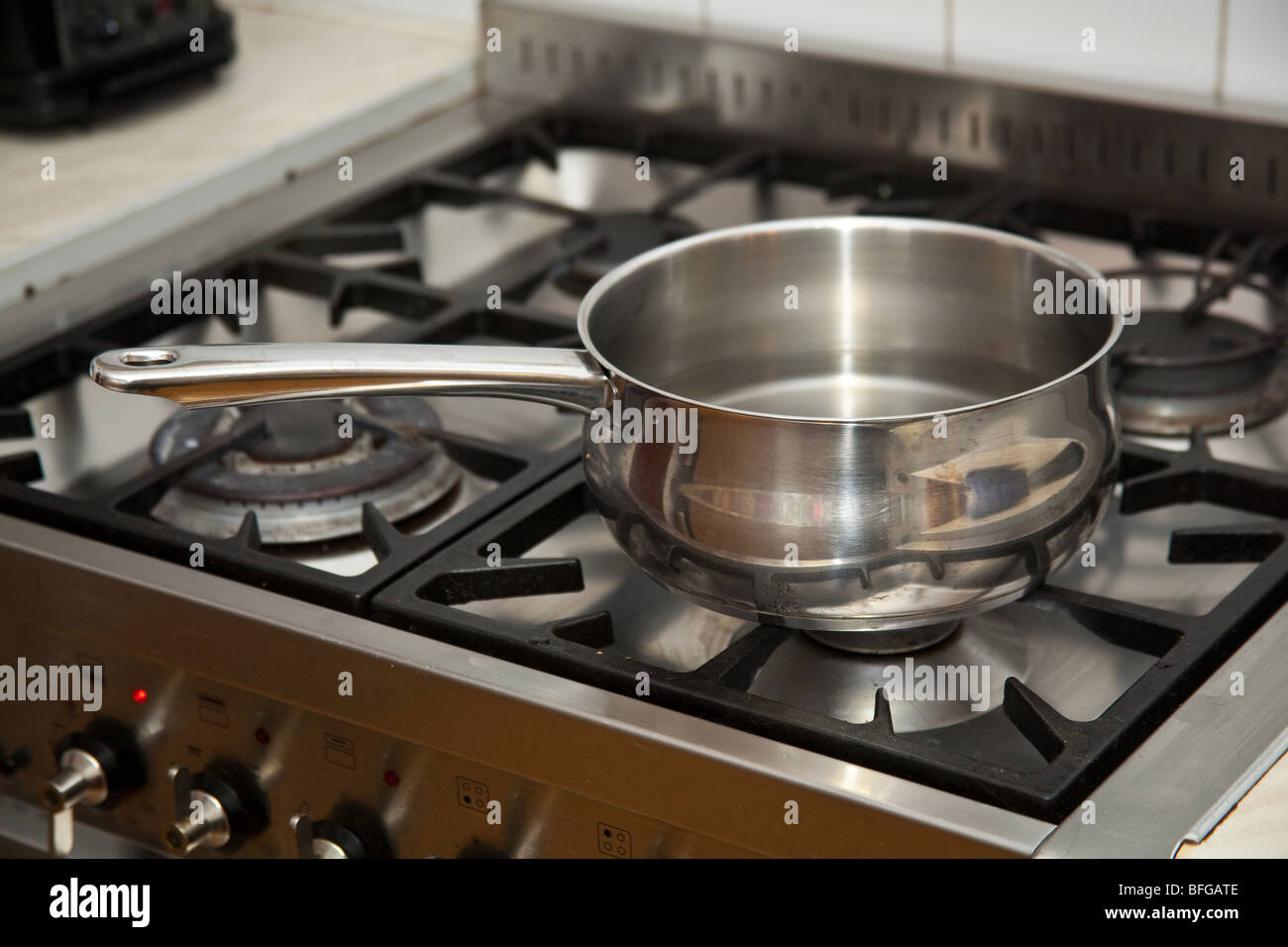 Pan of water boiling on a gas stove. - Stock Image