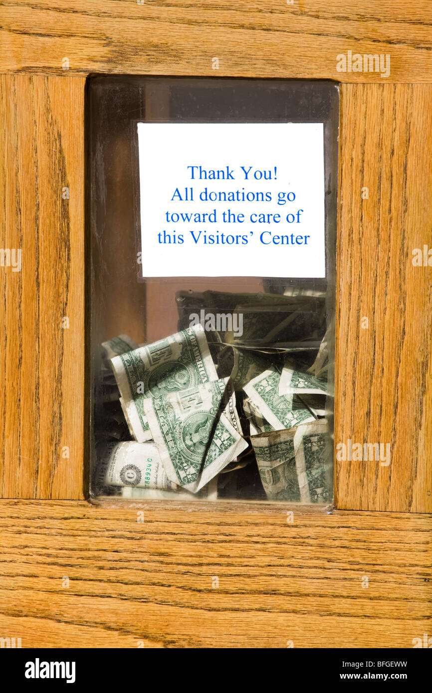 A donations box with dollar bills visible behind the glass window: All donations go toward the care of this Visitor's - Stock Image