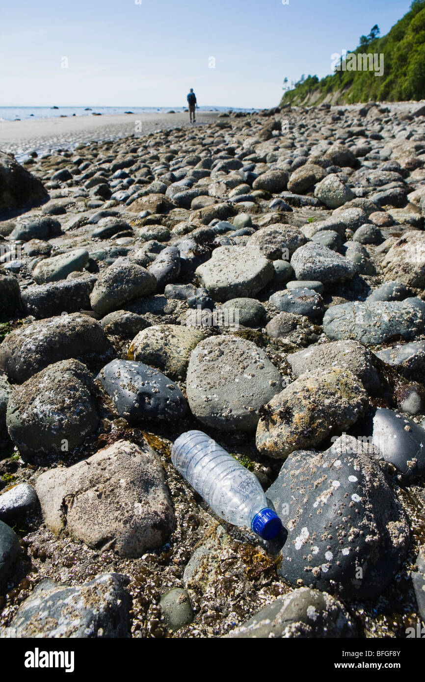 A single use clear plastic water bottle discarded on a rocky shoreline. - Stock Image