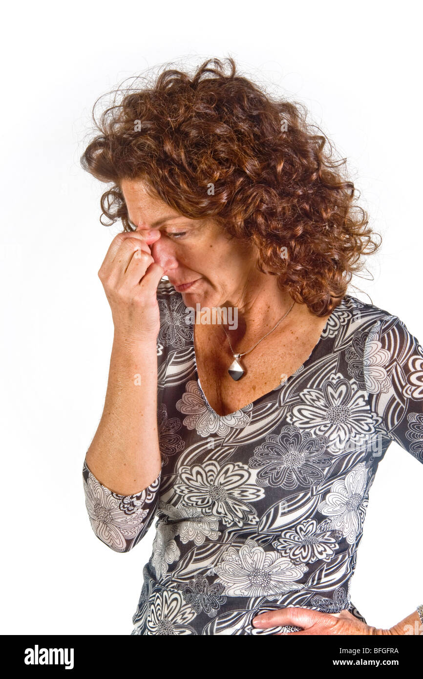 Pinching the bridge of her nose with closed eyes indicates a mood of negative evaluation in this woman. - Stock Image