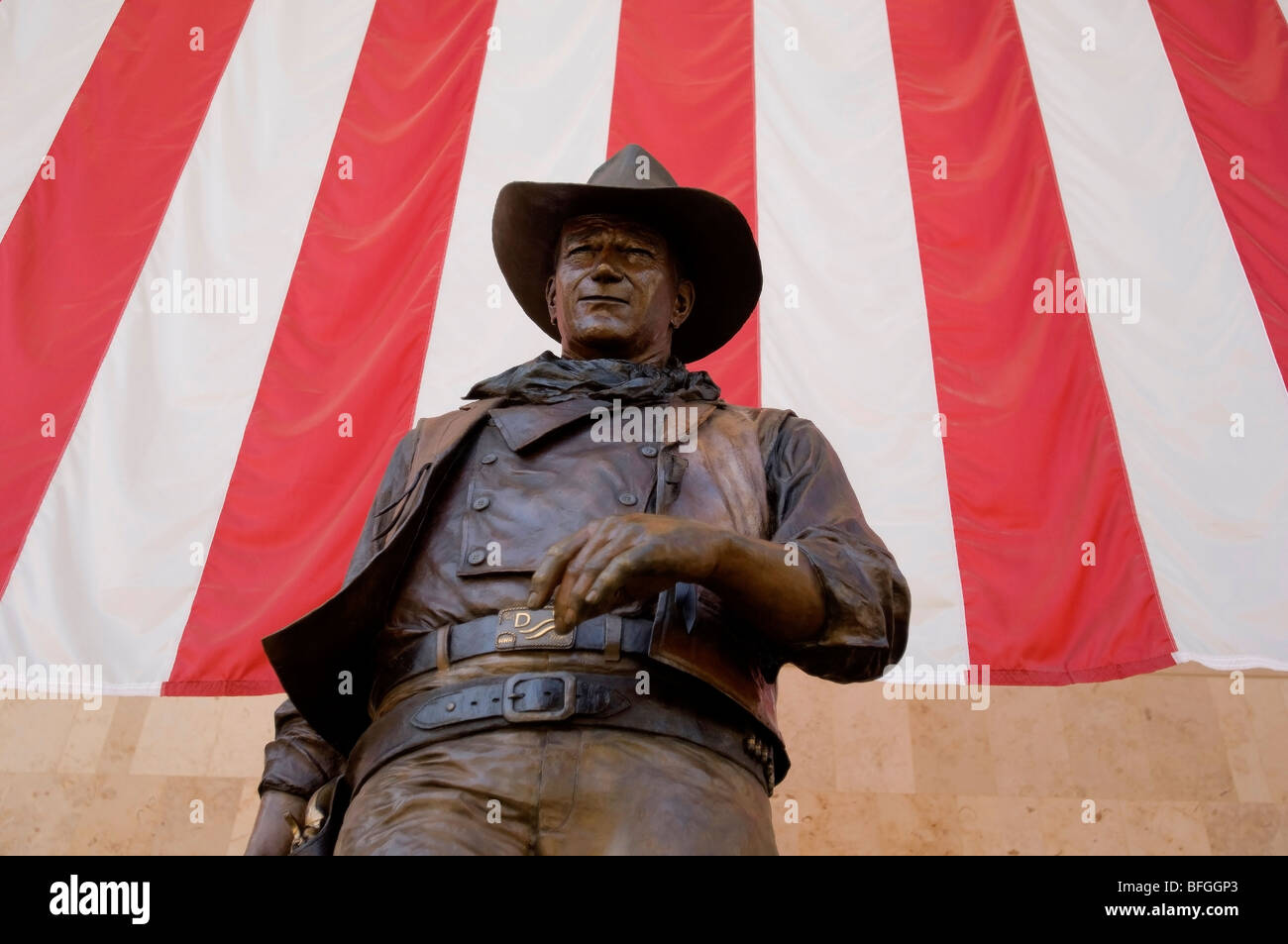 Statue of John Wayne in front of an American Flag located in the terminal at John Wayne Airport in Orange County, - Stock Image