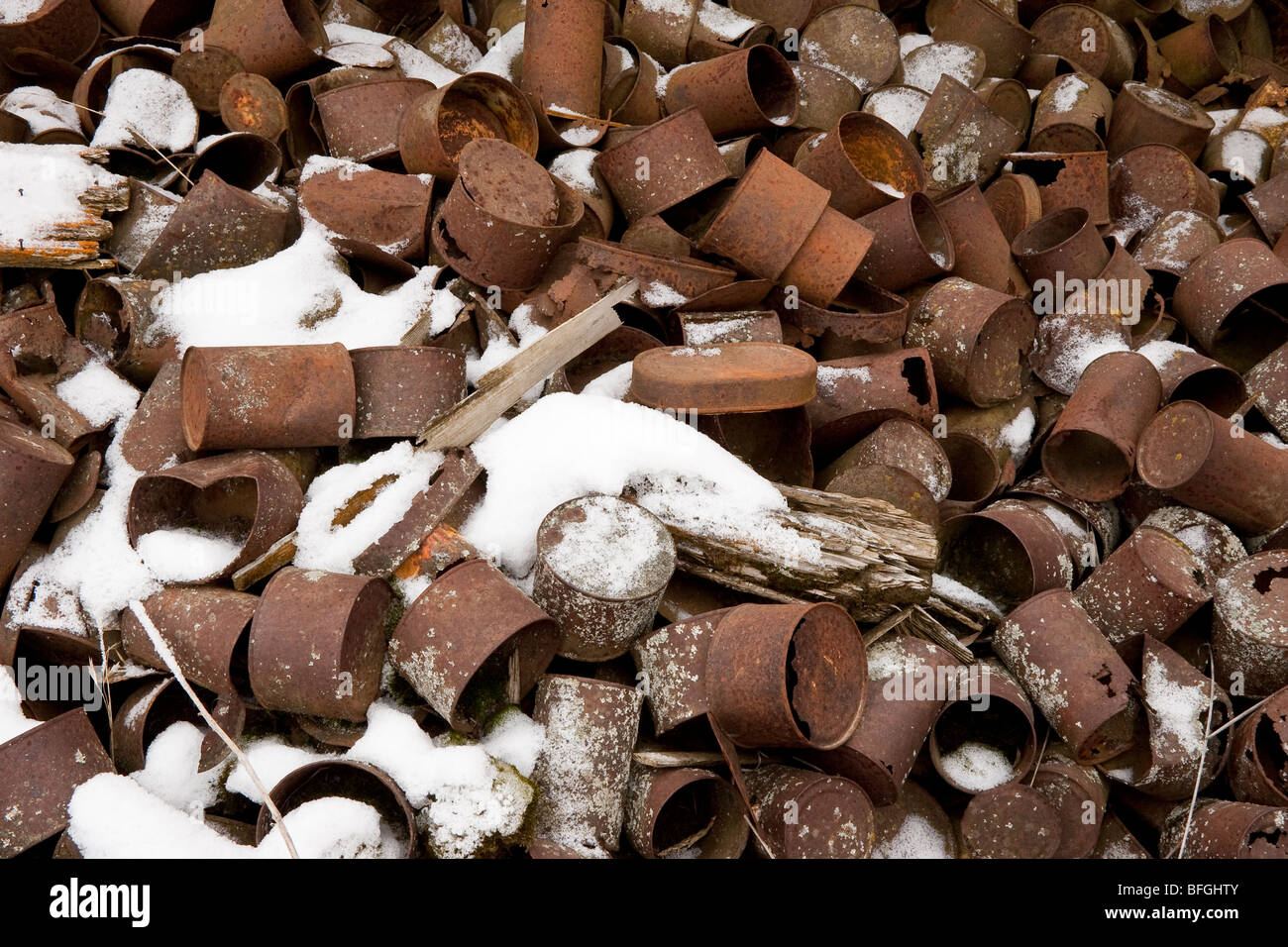 Pile of old rusting tin cans and fresh snow - Stock Image
