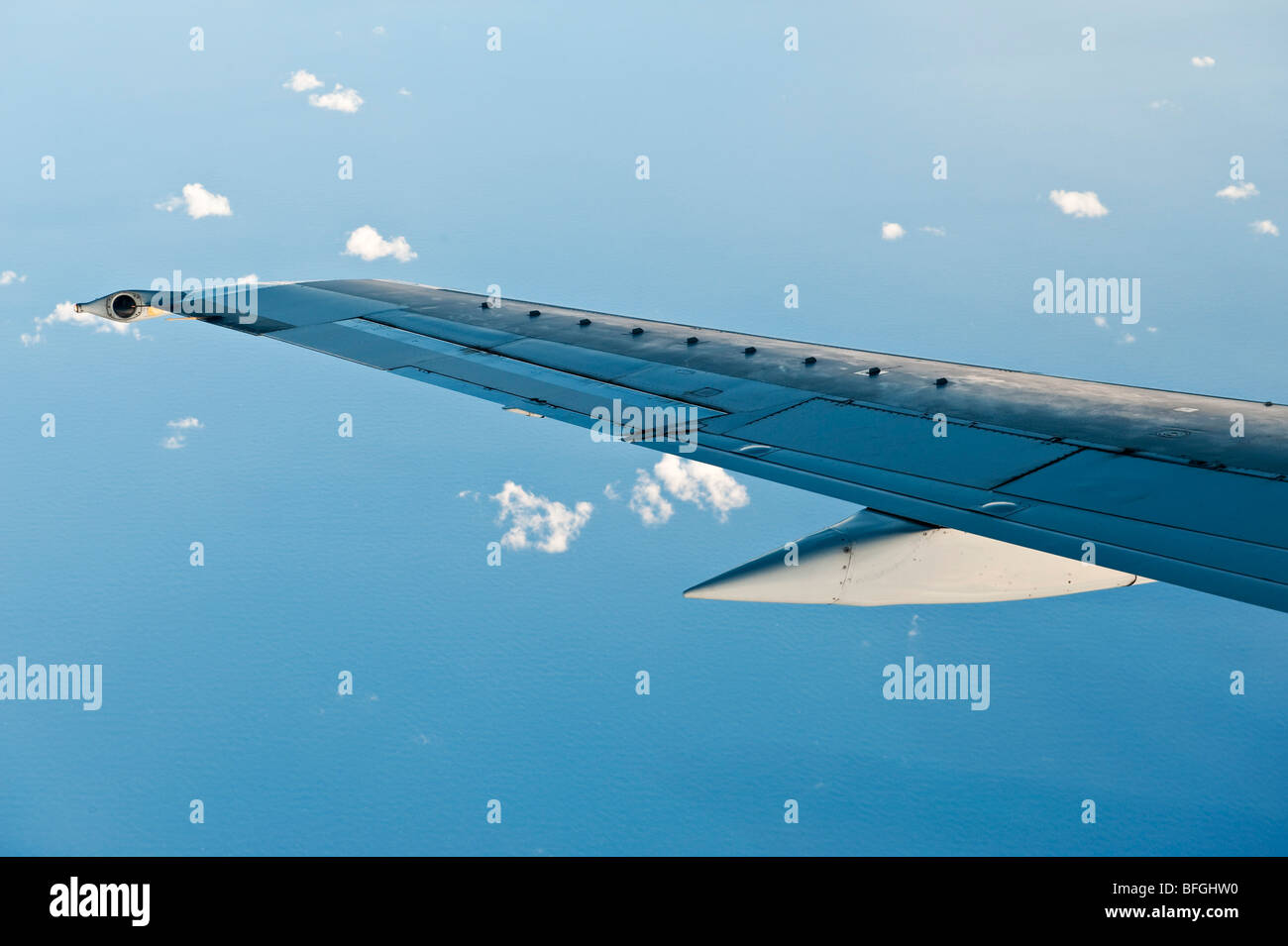 The wing of a Boeing 737 aircraft flying over the sea - Stock Image