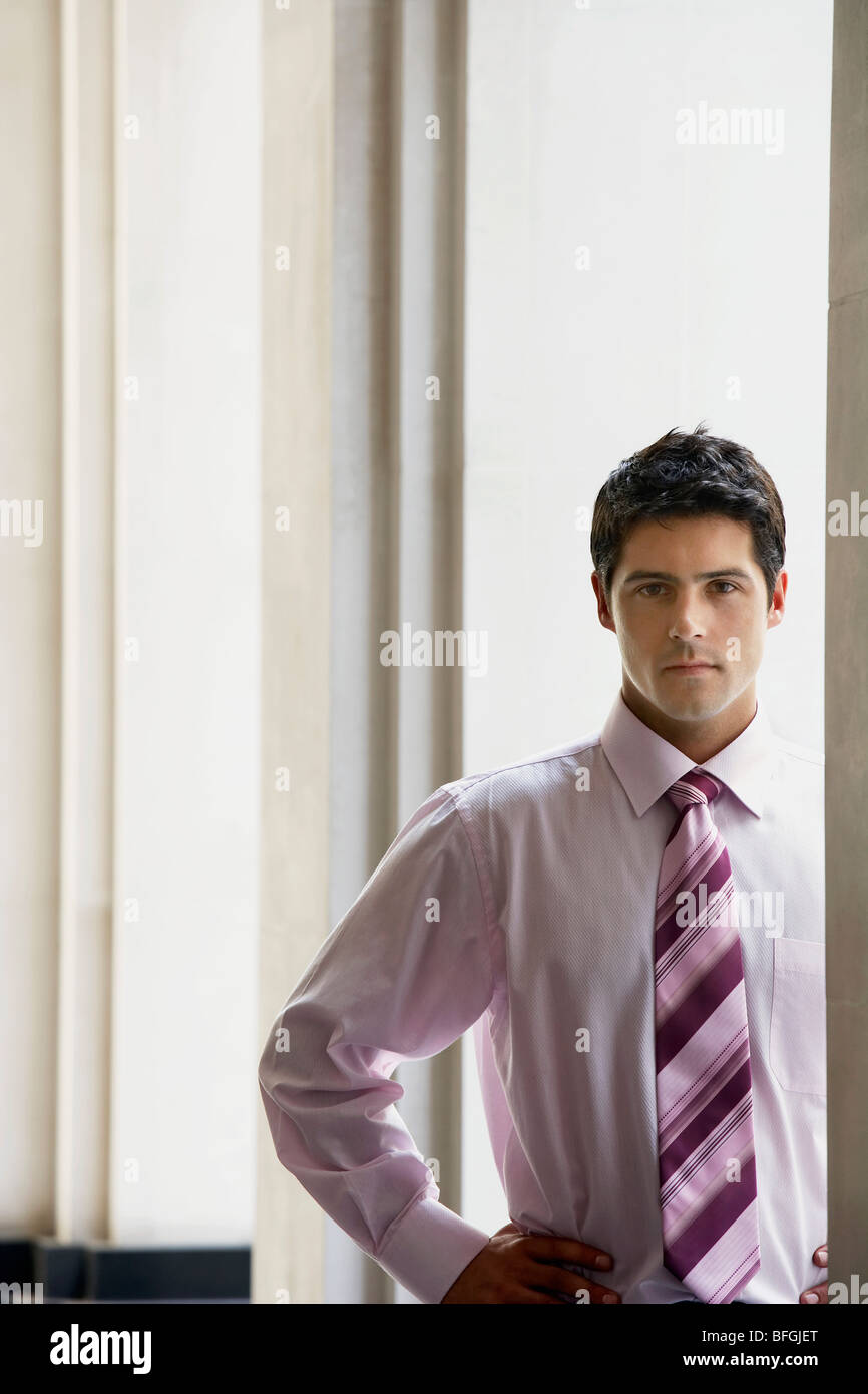 Serious businessman standing in archway, portrait - Stock Photo