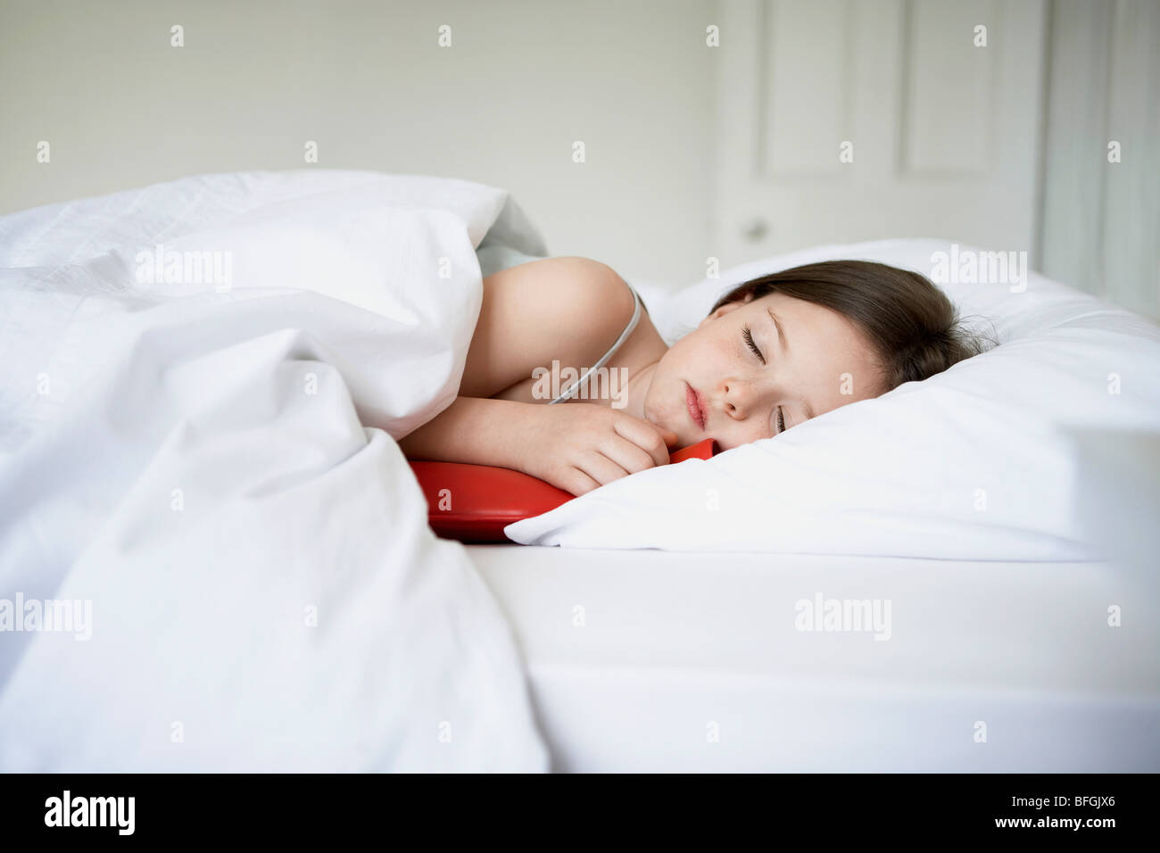 Little girl with cold in bed holding hot water bottle - Stock Image