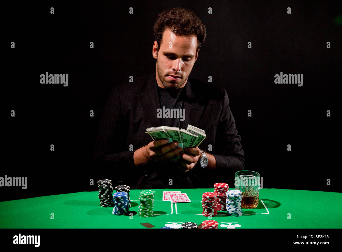 A young male gambler at the gambling table counts his money model release available - Stock Image