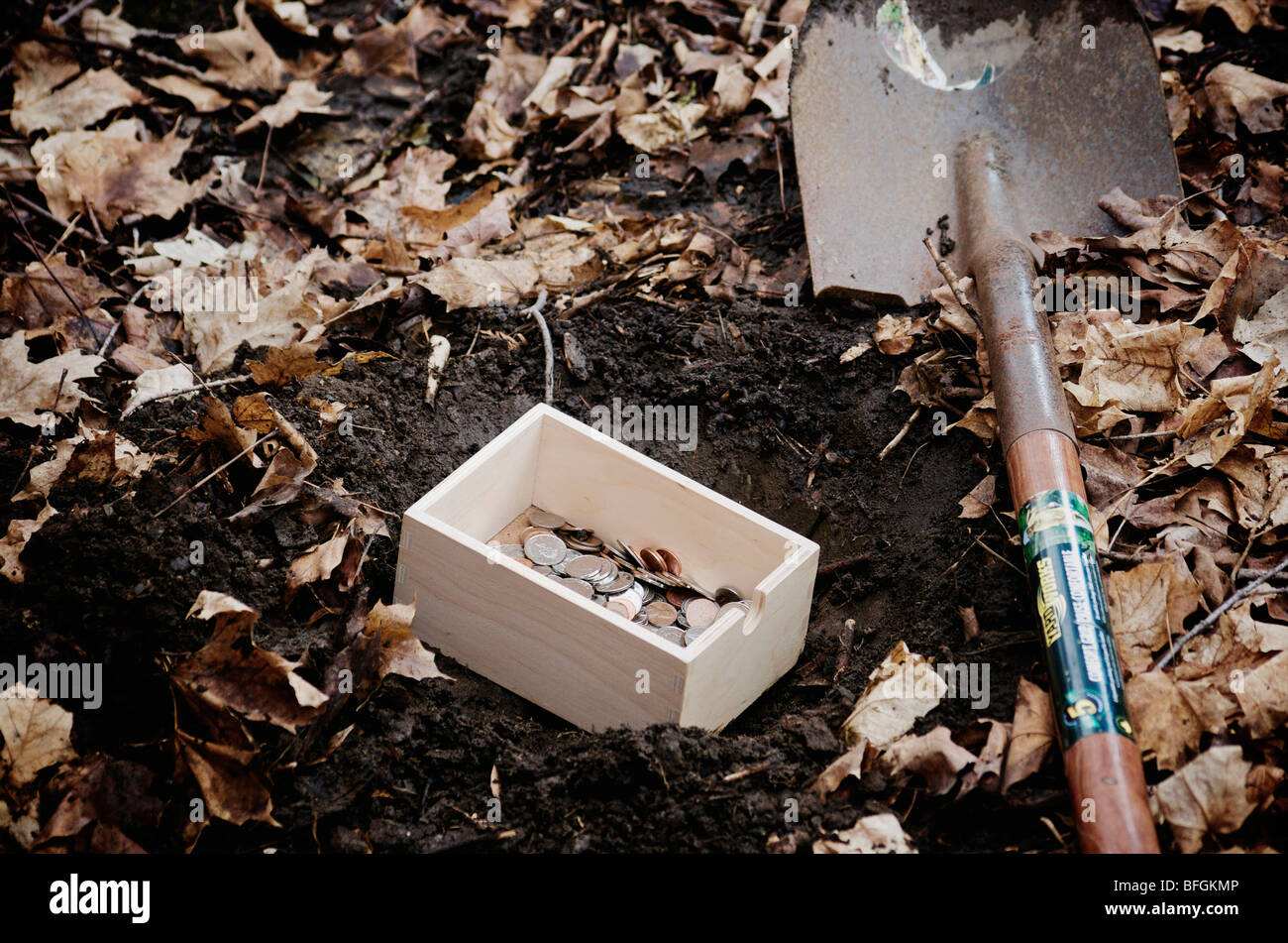 https://c8.alamy.com/comp/BFGKMP/shovel-next-to-a-box-filled-with-money-getting-buried-in-the-ground-BFGKMP.jpg