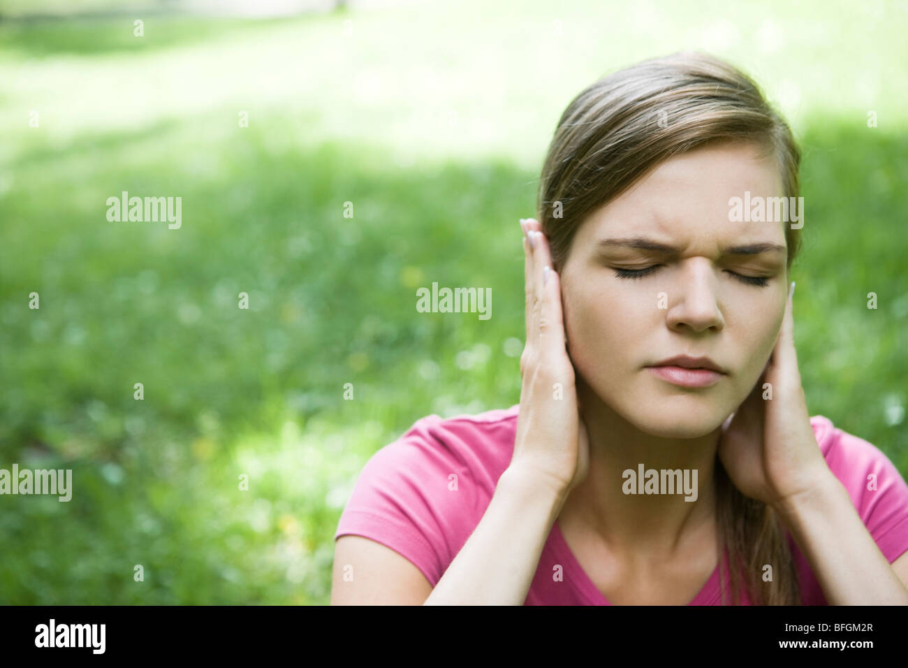 woman covering ears - Stock Image
