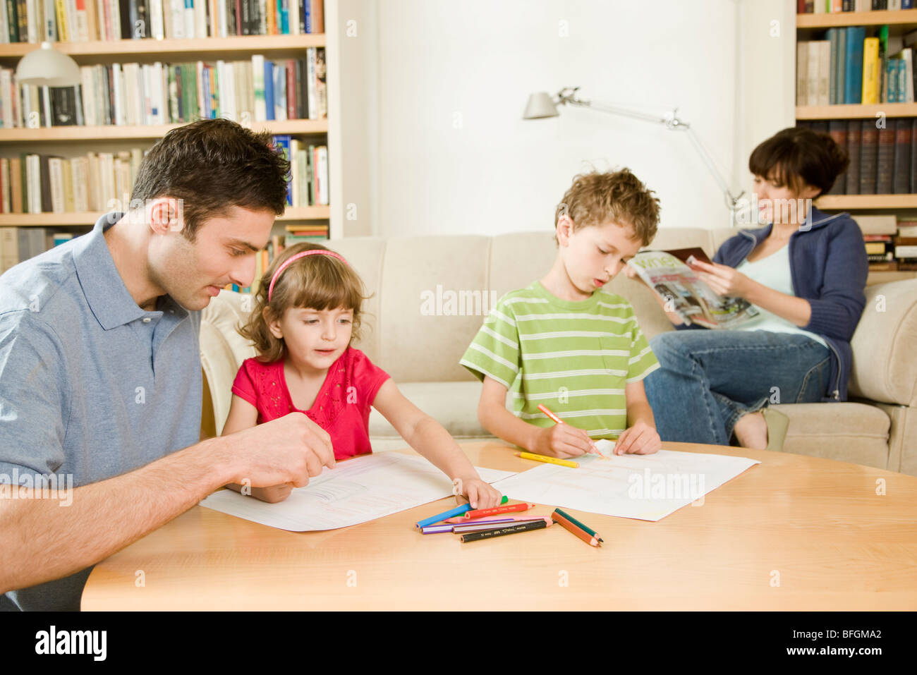 father playing with kids and mother relaxing Stock Photo