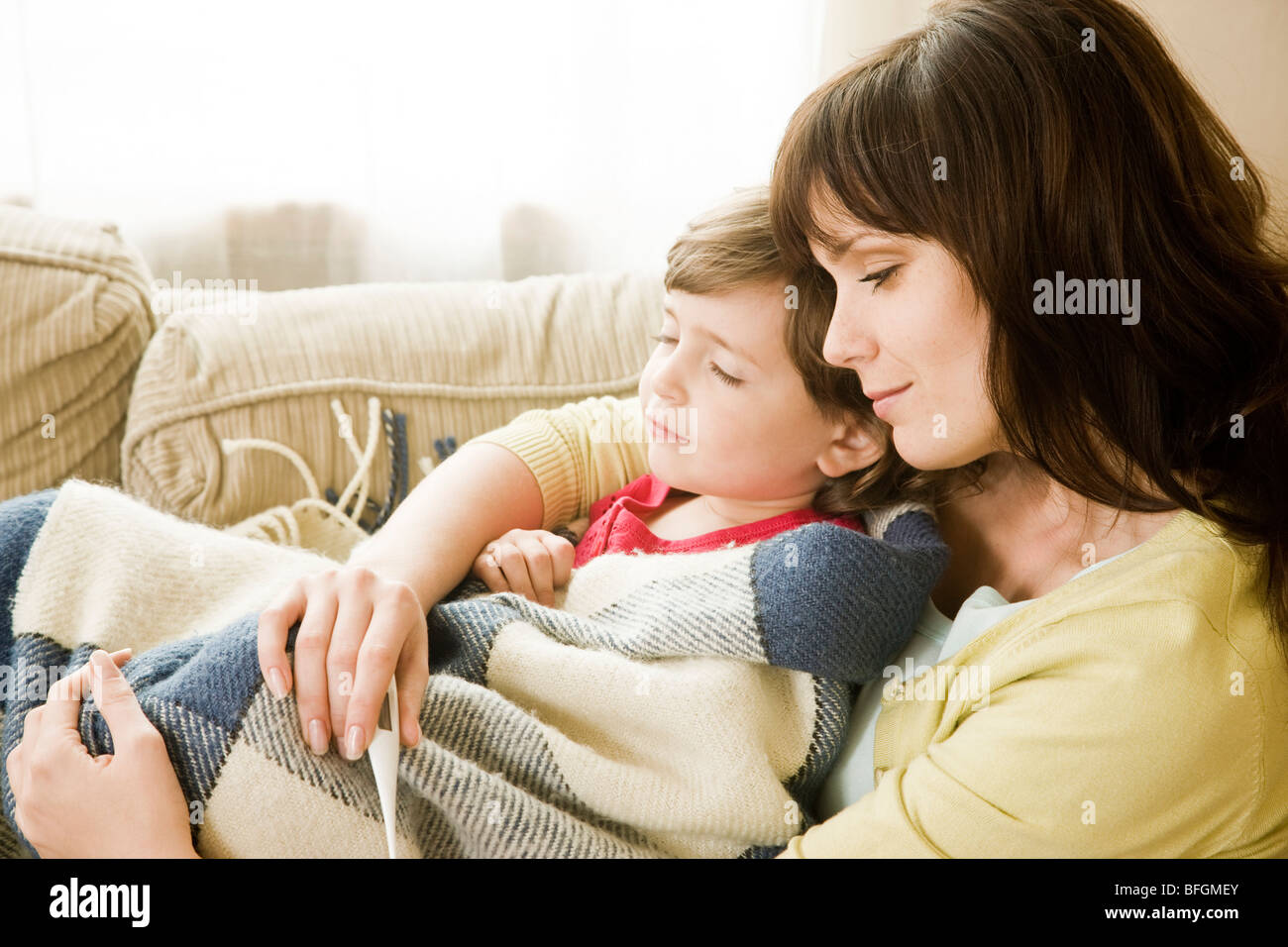 mother checking daughter temperature - Stock Image