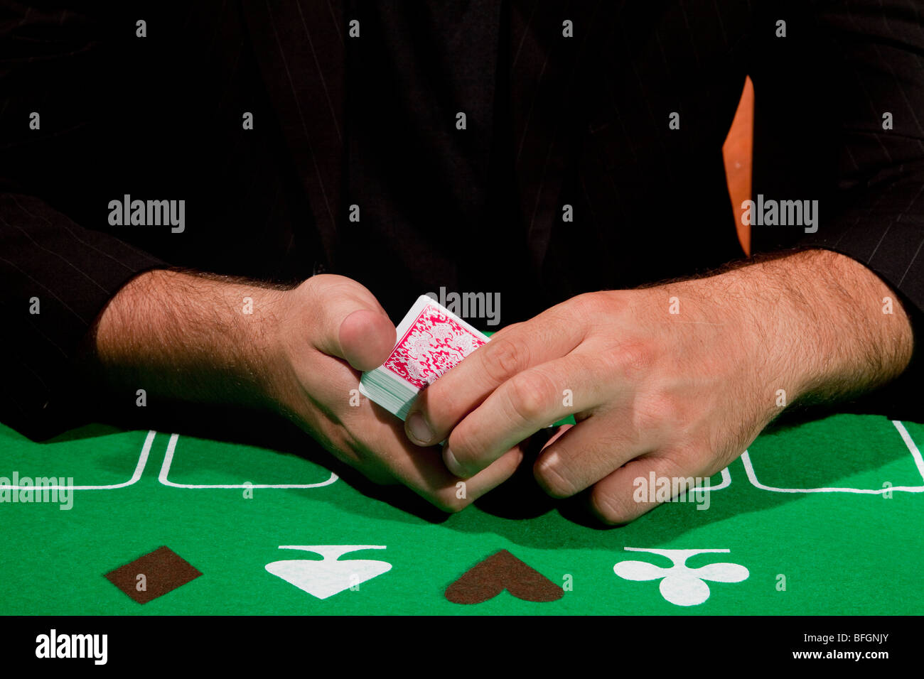 A young male gambler at the gambling table shuffles the card deck model release available - Stock Image