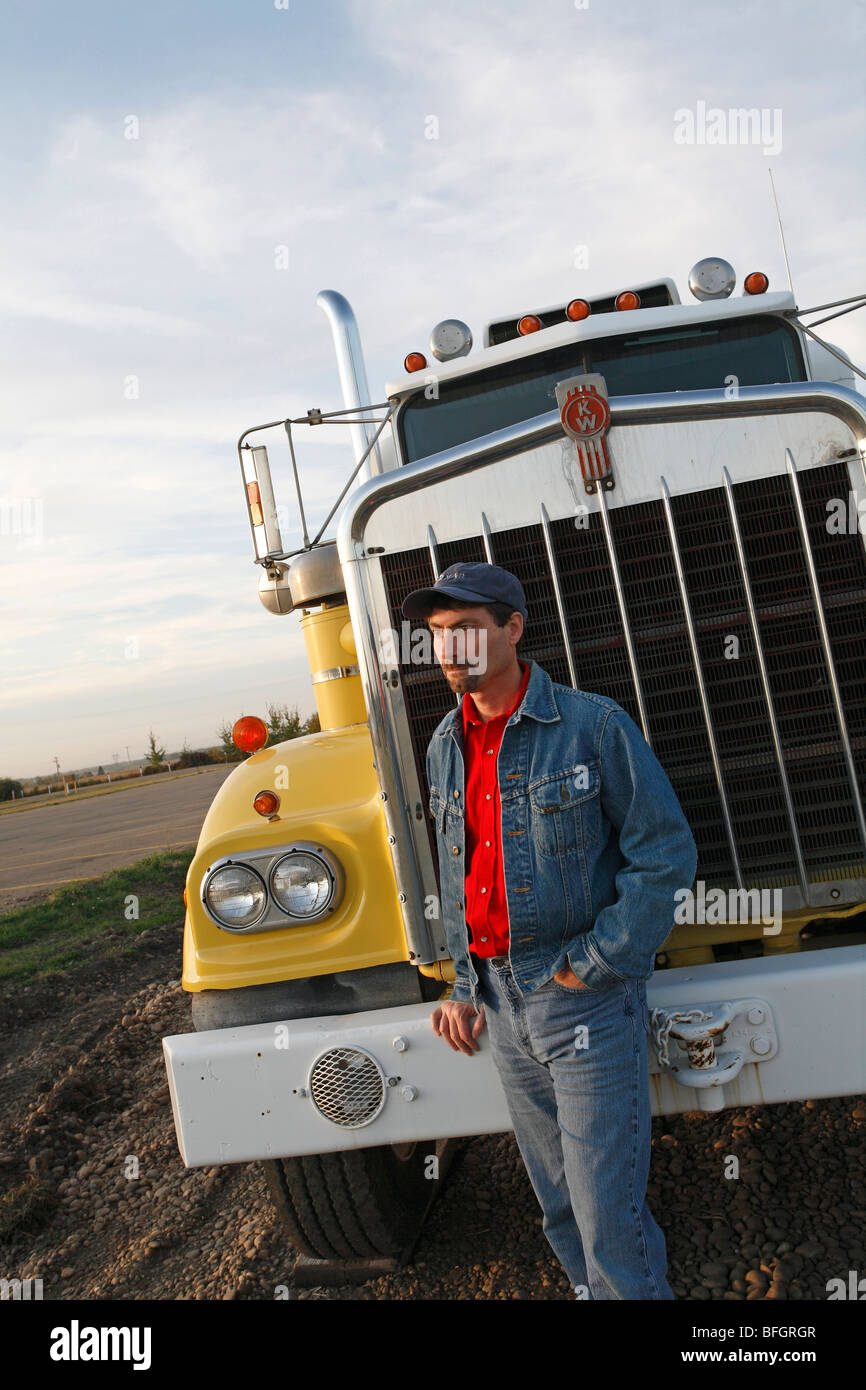 Truck driver standing next to long haul truck, Alberta, Canada - Stock Image