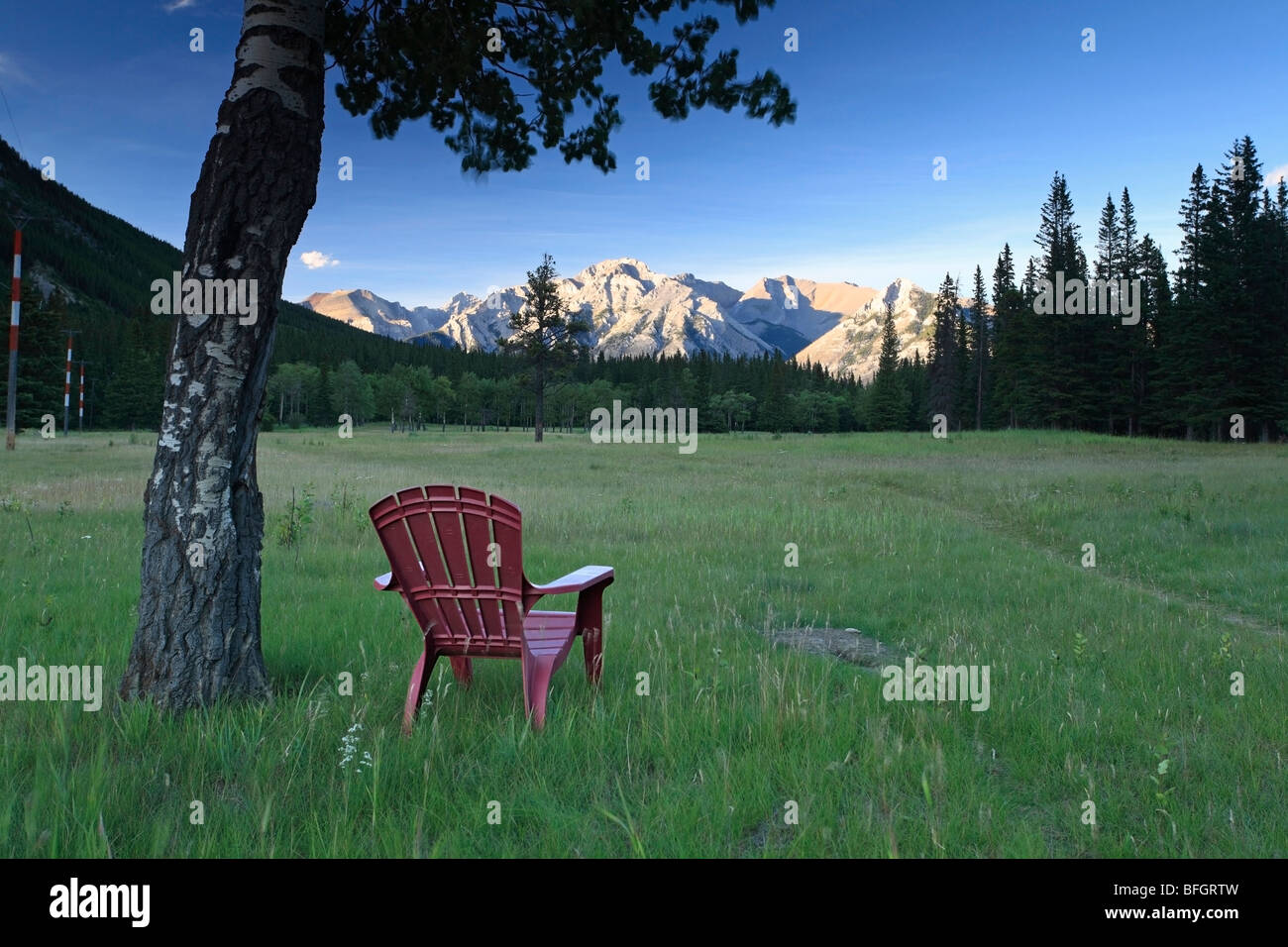 Chair in meadow overlooking Fairholm mountain range. Banff National Park, Alberta, Canada - Stock Image