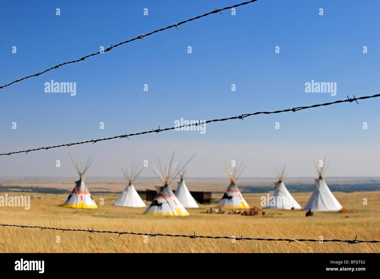 Indian teepees on prairie and barbed wire fence at Head Smashed in Buffalo Jump interpretive centre, Alberta, Canada - Stock Image