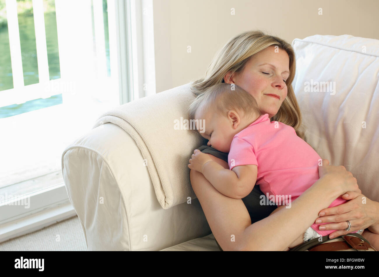 Mother with baby sleeping on sofa - Stock Image